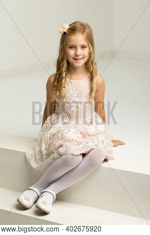 Lovely Girl Sitting On White Staircase. Portrait Of Beautiful Blonde Girl Wearing Nice Dress, Tights