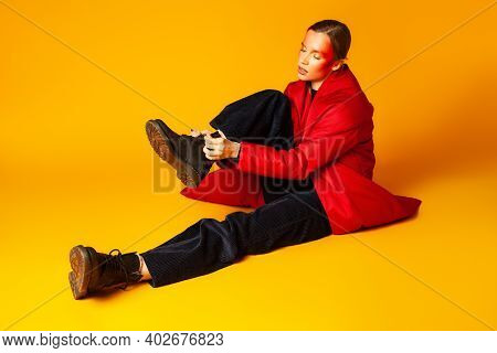 Trendy Woman Tying Shoelaces On Boot Against Yellow Background
