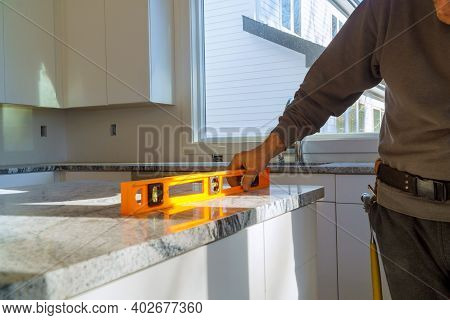 Under Construction With Worker Checks The Leveling Of A Granite Slab For Use In A Home Kitchen Remod