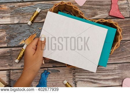 Blank Card Held By Female Hand. Table With Craft Items. Valentines Day Card.