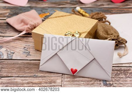 Letter Envelope On A Wooden Table With Craft Materials.