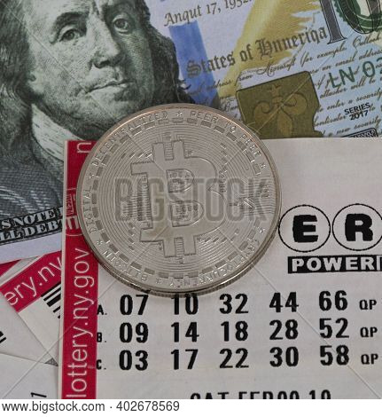 Babylon, New York, Usa - 10 January 2021: One Silver Bitcoin Coin On Top Of Lattery Tickets And One