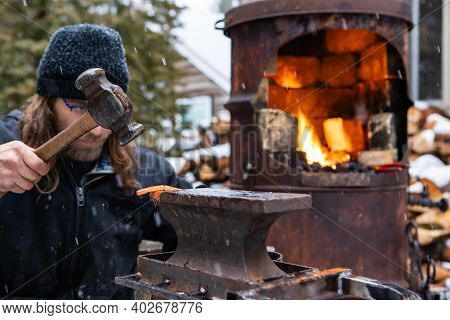 Close Up Shot Of A Young Man, Very Concentrated In Hammering A Red, Sizzling Hot Rod Of Iron Out Of