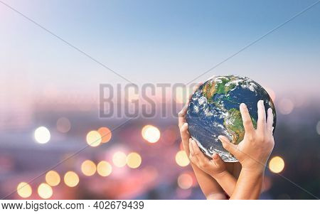 World Environment Day Concept: Family Hands Holding Earth Global Blurred City Night Background. Elem