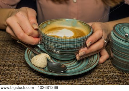 A Ladys Hands With Latte Coffee On A Wood Table