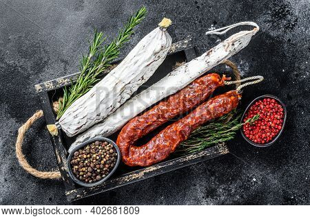 Spanish Dry Cured Sausages Salami, Fuet And Chorizo In A Wooden Tray. Black Background. Top View