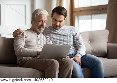 Happy Adult Son And Senior Dad Use Laptop At Home