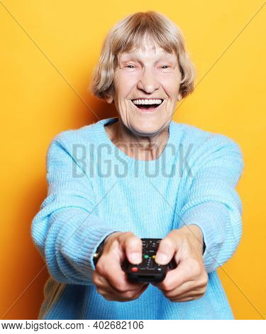 lifestyle and people concept: funny grandma is holding a TV remote over yellow background