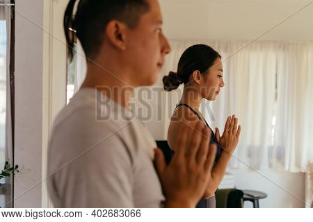 Side View Of Asian Man And Woman Gesturing Namaste And Meditating While Practicing Yoga At Home Toge