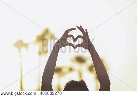 Two Hands Fingers Palms Folded In The Shape Of A Heart On A Background Of Sunset And Palm Trees In B