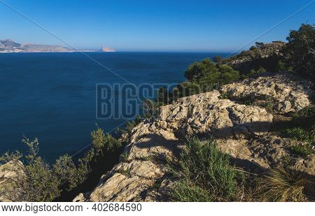 View Over The Ocean To The Rock Ifach Of Calpe With Steep Overgrown Cliffs From Natural Park Serra G