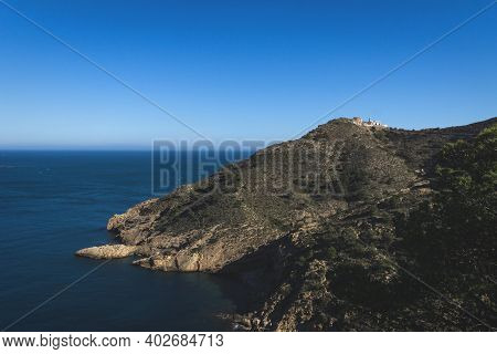 Lighthouse On Rocky Cliffs In Deep Blue Ocean Bay In The Natural Park Serra Gelada In Albir, Costa B