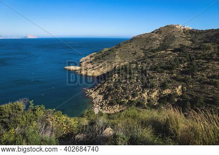 Sunny Bay In The Natural Park Serra Gelada With Lighthouse And The Rock Ifach Of Calpe In The Backgr