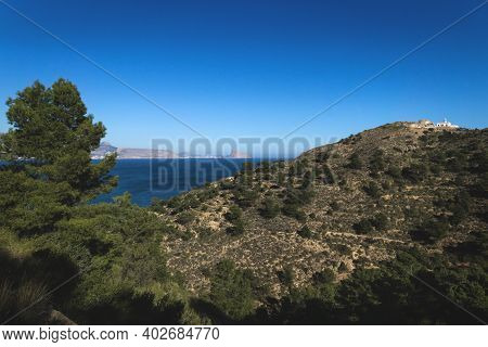 Sunny Panoramic View Of Natural Park Serra Gelada With Lighthouse And The Rock Ifach Of Calpe In The