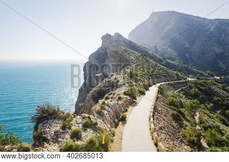 Scenic Walking Path Along Steep Cliffs Covered With Bushes Along The Ocean In The Natural Park Serra