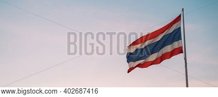 Banner Of Thai Flag Fluttering With Wind Blow In Clear Sunset Sky Background With Negative Copy Spac