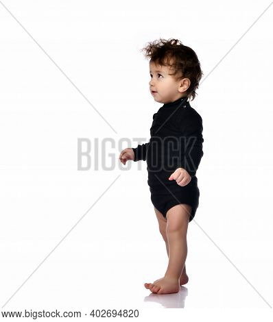Boy Walks Making The First Step. Cute Barefoot Baby Learns To Walk. Isolated Portrait Shot Against A