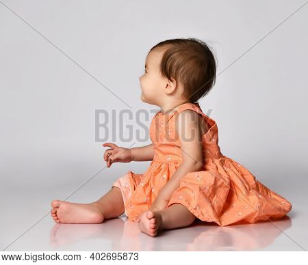 Little Girl In A Pink Dress Sits Barefoot On A Gray Background And Looks Away From The Camera. Conce