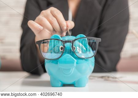 Close-up A Blue Piggy Bank Wearing Black Glasses On The Wooden Table. The Symbol Of Saving Money And