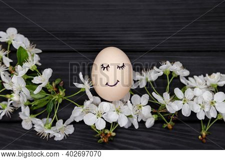 Easter Egg Painted In Pastel Colors With Cute Face. White Blooming Cherry Branches On Black Wooden B