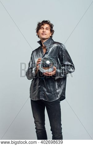 Portrait Of A Tall Attractive Man With A Mirror Disco Ball On A White Background.