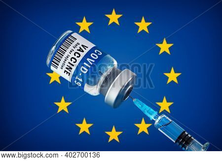 COVID-19 vaccine and syringe in front of european flag. Concept of corona virus treatment, injection, vaccination in european union