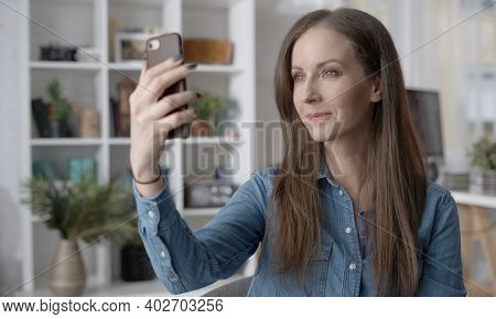 Happy white woman talking on video chat with phone at home. Conference call with friend, family or work. Video blogger working, sitting in living room, taking selfie.
