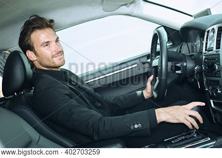 Happy young businessman traveling driving luxury car, smiling. Limousine service, chauffeur.