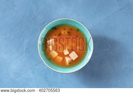 Miso Soup With Tofu And Scallions, Shot From Above On A Blue Background