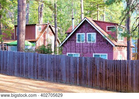 Rustic Cabins Besides A Wooden Fence Surrounded By An Alpine Coniferous Forest Taken At A Residentia