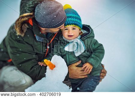 Portrait of a Happy Father with His Cute Little Son Building Snowman Together. Enjoying Winter Time. Happy Christmastime Holidays.