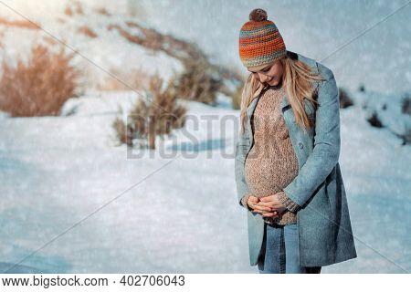 Nice Pregnant Woman Walking in the Countryside in Winter. Looking on the Tummy and Talking to the Baby. Happy Healthy Pregnancy.
