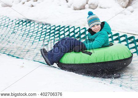 Child Having Fun On Snow Tube. Boy Is Riding A Tubing. Winter Entertainment. Kid Sliding Downhill On