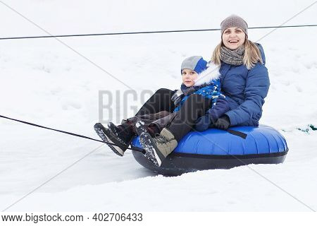 Family Having Fun On Snow Tube. Mother With Kid Is Riding A Tubing. People Sliding Downhill On Tube.