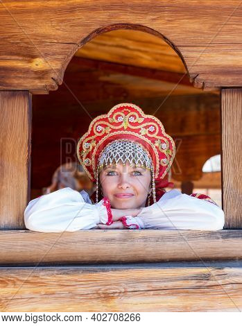 Portrait Of Girl In Russian Authentic National Red Clothes On Wooden Background