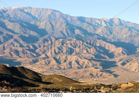 Sun Setting On Arid Mountainous Terrain With Mt San Gorgonio Beyond Taken In The Mojave Desert, Ca