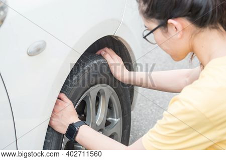 Cropped Shot Of Young Woman Touching And Checking Her Car Tyre. She Worrying About Somethings Wrong