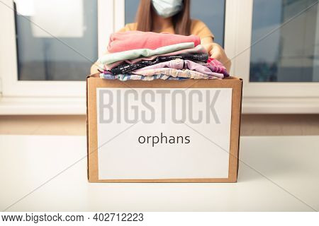 A Young Woman At A Charity Foundation Holds A Box Of Clothes For Orphans
