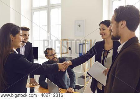 Happy Business People Closing Deal And Shaking Hands After Negotiation Meeting In Office