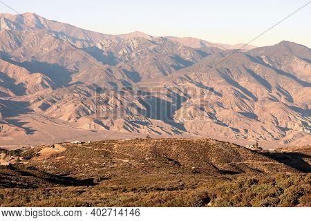 Sunset On Arid Grasslands With Barren Mountains Beyond Taken On A Rural High Desert Plateau At The S