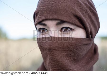 A Woman In A Burqa Looks Into The Distance. A Woman In A Hijab. A Day Of Hijab And Chastity