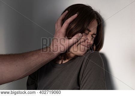 A frightened young woman is propped by her partner's hand against the wall. She suffers from beatings and domestic violence. The man abuses his wife at home. A marriage quarrel ends with violence.