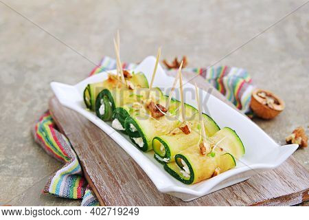 Roasted Zucchini Rolls Stuffed With Cream Cheese And Nuts On A White Plate On A Gray Concrete Backgr