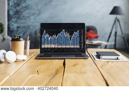 Closeup Of Laptop With Stock Market Analyst Monitor And Cups, Headphones, Coffee On A Table In A Caf