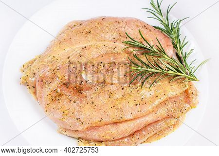 Marinated Chicken Fillet On A White Plate With Marinated Herbs. Thinly Sliced Chicken Fillet.