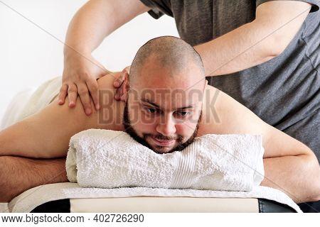 Massage Studio. Sports Massage. Massage Therapist Massaging Shoulders Of A Male Athlete, Working Wit