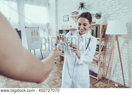 Male And Female Doctors With Stethoscopes In Office. Doctor Is Taking Money.