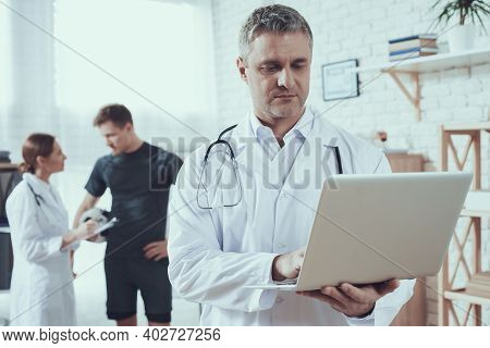 Male And Female Doctors With Stethoscopes In Office. Doctor With Laptop With Athlete In Background.