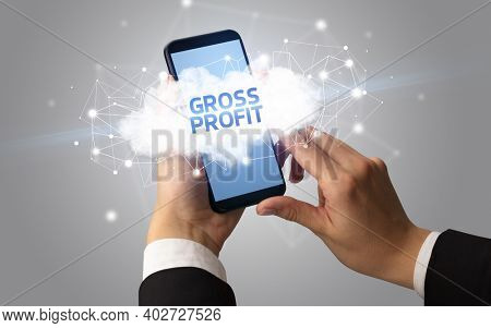 Female hand touching smartphone with GROSS PROFIT inscription, cloud business concept