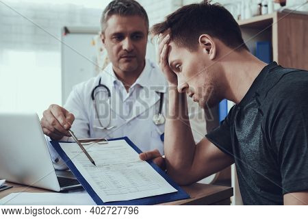 Male And Female Doctors With Stethoscopes In Office. Athlete Is Filling Form On Clipboard.